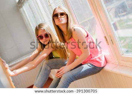 closeup portrait of hugging 2 beautiful blond young women having fun happy smiling on sunny windows background - stock photo