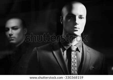 Closeup portrait of illuminated bald-headed fashion mannequin wearing casual male suit made of thready cloth jacket nasal in tone tie shirt over blur one black and white, horizontal picture    - stock photo