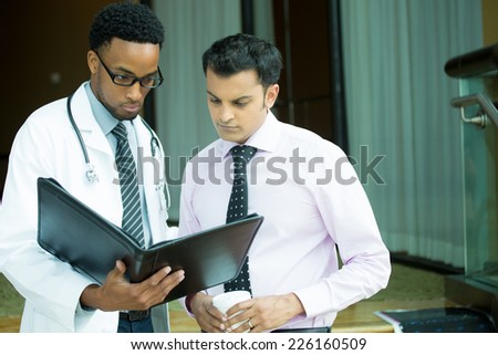 Closeup portrait of intellectual healthcare professional with white labcoat, looking at notes, discussing findings with patient, isolated hospital clinic background - stock photo