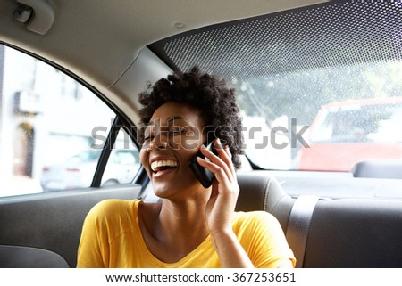 Closeup portrait of laughing young african woman sitting on a back seat of a car and talking on mobile phone  - stock photo