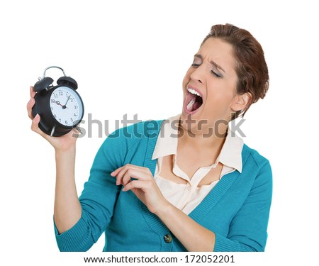Closeup portrait of lazy sluggish overtaxed overworked weary tired young woman holding clock yawning, isolated on white background. Negative emotion facial expression feeling, body language. - stock photo