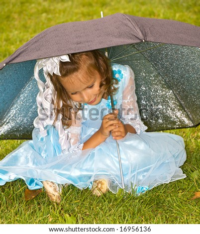 closeup portrait of little girl sitting under umbrella on green grass