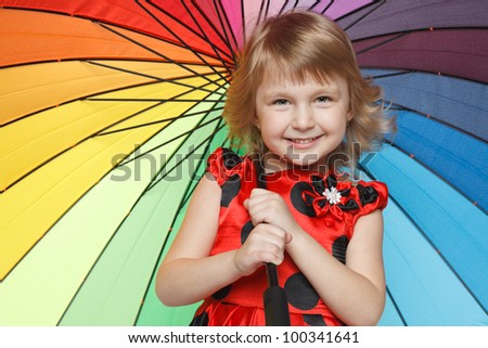 Closeup portrait of little girl standing under colorful umbrella