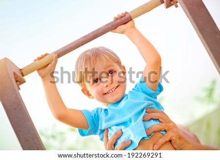 Closeup portrait of little happy boy lifting on crossbar, daddy help his son doing physical exercise outdoors, happy and healthy childhood concept