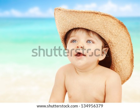 Closeup portrait of little naked cowboy wearing stetson hat over seascape background, happy child playing on the beach, joy and fun concept - stock photo
