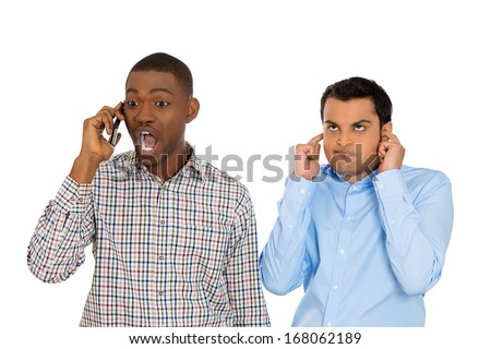 Closeup portrait of loud obnoxious rude guy talking loudly on cell phone, man next to him is pissed off and closes ears. Isolated on white background. Negative emotion facial expression feelings - stock photo