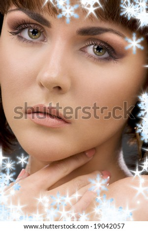 closeup portrait of lovely green-eyed woman with snowflakes - stock photo