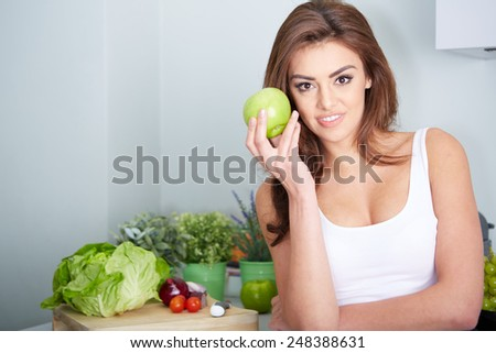 Closeup portrait of lovely young brunette woman biting juicy fresh delicious apple against gray background. Beautiful young lady eating healthy food. - stock photo