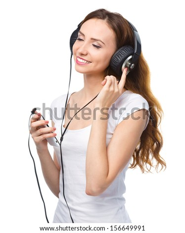 Closeup portrait of lovely young woman closing her eyes and enjoying music using headphones, isolated over white - stock photo