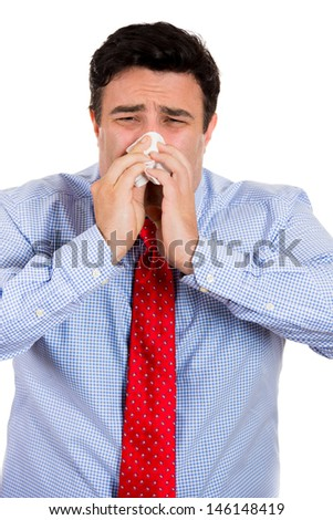 Closeup portrait of male with cold and blowing nose in kleenex, isolated on white background  - stock photo