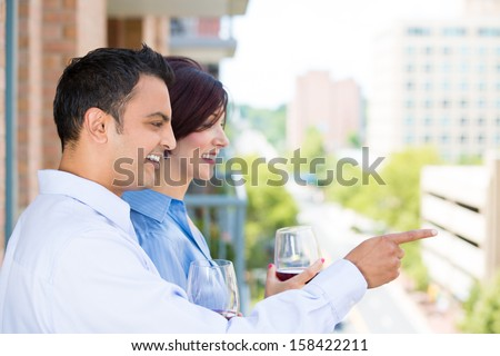 Closeup portrait of man and woman drinking wine and enjoying life on outside balcony, isolated on a city background with trees and buildings - stock photo