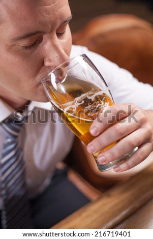 closeup portrait of man drinking beer. man holding glass of light beer - stock photo