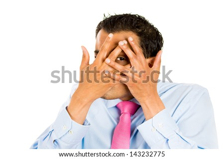 Closeup portrait of man so afraid he can only look through a peephole with his hands covering face, isolated on white background - stock photo