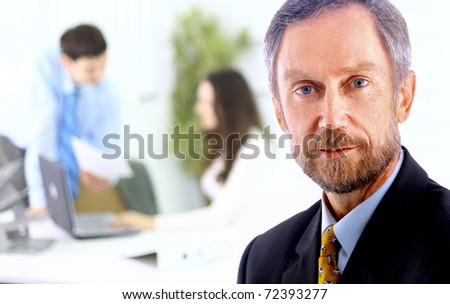 Closeup portrait of mature business man with colleagues at the back - stock photo