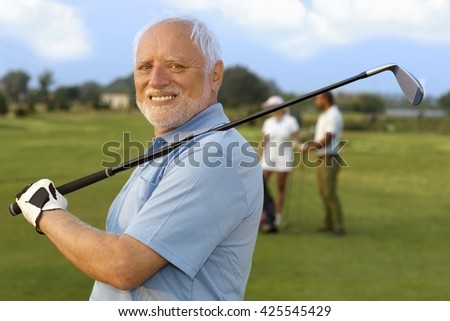 Closeup portrait of mature male golfer holding golf club, smiling happy, looking at camera. - stock photo