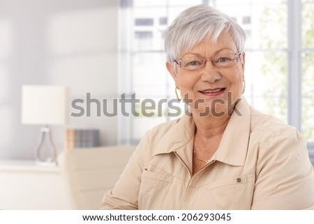 Closeup portrait of mature woman at home, smiling, looking at camera. - stock photo