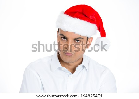 Closeup portrait of mean young man in red santa claus hat arms looking pissed off angry at you camera gesture , isolated on white background with space to left. Negative emotion facial expression
