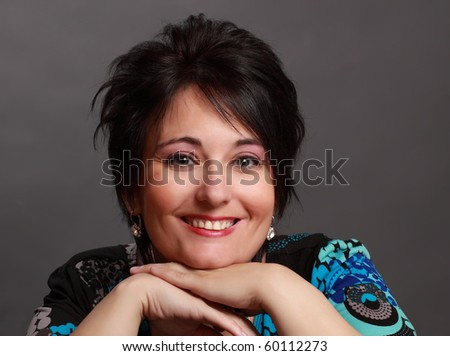 closeup portrait of middle aged woman, blue background - stock photo