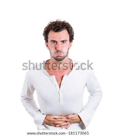 Closeup portrait of miserable, upset, young man, doubling over in acute body stomach pain, looking very sick, isolated on white background. Negative facial expressions, emotion feelings, health issues - stock photo