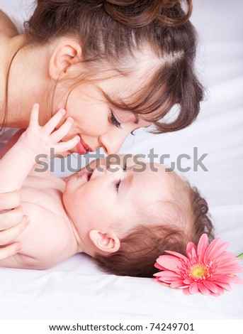 Closeup portrait of mother and baby enjoying time with each other - stock photo