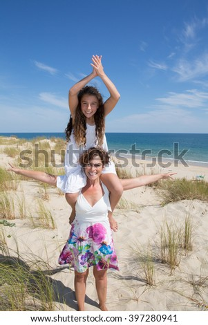 Closeup portrait of mother and her daughter having fun on tropical beach - stock photo