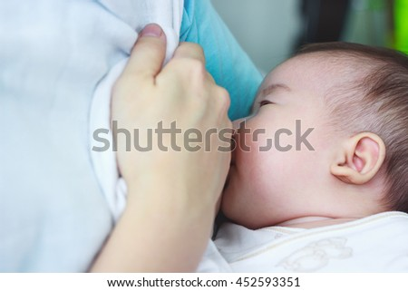 Closeup portrait of mother breastfeeding her newborn baby with breast milk. Drinking milk for good health. Concept about the growth of children.