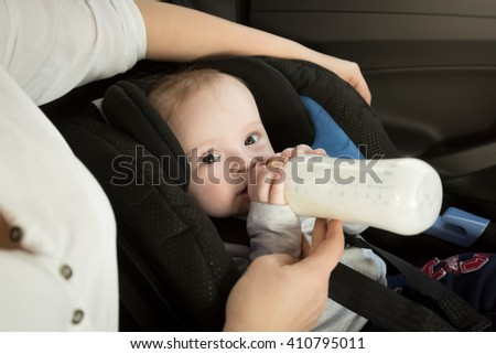 Closeup portrait of mother feeding baby in car from bottle - stock photo