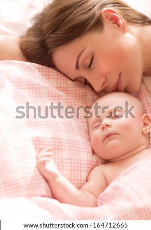 Closeup portrait of mother with child sleeping at home, bedtime, female with newborn baby asleep, health care, happy motherhood concept