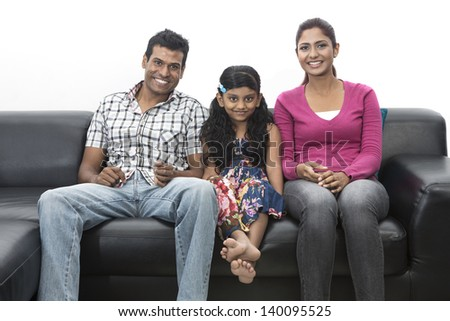 Closeup portrait of mum, dad and child relaxing at home on sofa watching TV. - stock photo