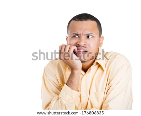 Closeup portrait of nervous young man biting his nails and looking away with a craving for something or anxious, isolated on white background. Negative human emotion facial expression feelings