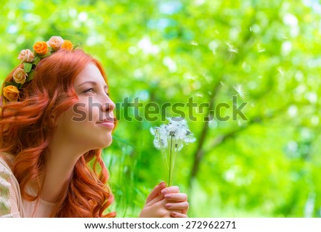 Closeup portrait of nice happy woman holding in hands dandelion flowers, having fun in fresh green park, enjoying beauty of spring nature - stock photo
