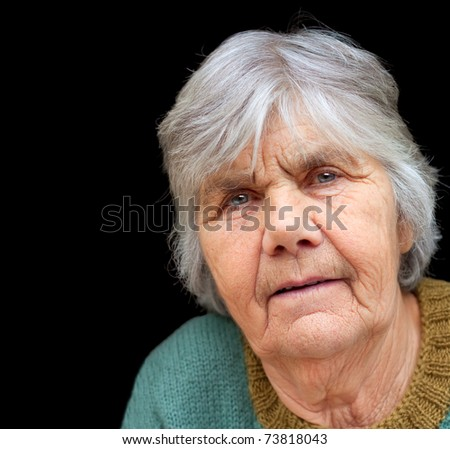 Closeup portrait of nice senior woman isolated on black background - stock photo