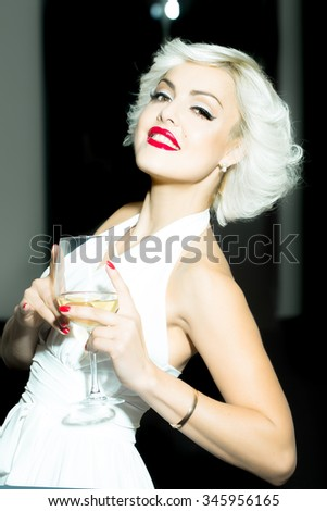 Closeup portrait of one attractive sensual smiling sexy young retro woman with blonde hair red lips in white dress in monroe style indoor with glass of wine on blurred background, vertical picture - stock photo