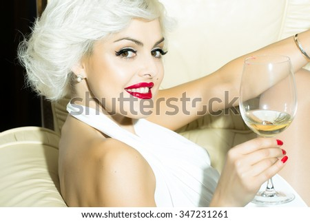 Closeup portrait of one attractive sensual smiling sexy young retro woman with blonde hair red lips in white dress in monroe style indoor drinking glass of wine sitting in chair, horizontal picture - stock photo