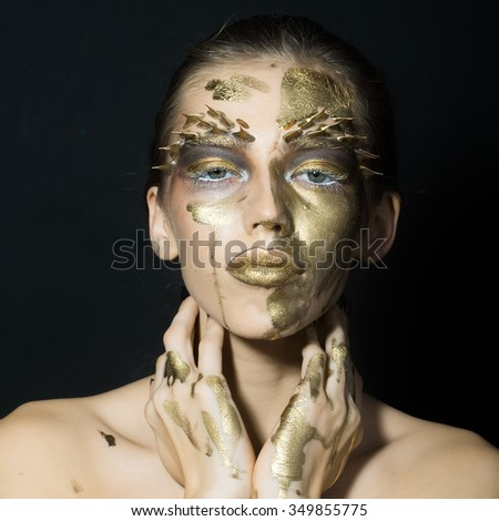 Closeup portrait of one beautiful sexy wild young woman with bright golden animal makeup with thorns on face in studio on black background, square picture