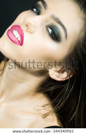Closeup portrait of one beautiful young sexual woman with long wet curly hair and bright makeup looking forward indoor on studio background, vertical picture