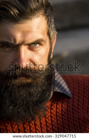 Closeup portrait of one handsome senior serious man with long black beard in red sweater looking forward sunny day outdoor on natural background, vertical picture - stock photo