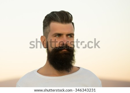Closeup portrait of one handsome young stylish thoughtful man with long dark lush beard in white sweater looking away standing outdoor on light sky background, horizontal picture - stock photo