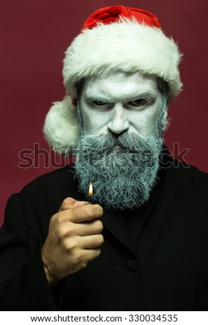 Closeup portrait of one senior frozen new year man with painted face in white and long beard in christmas santa red hat holding cigarette lighter in studio on black background, vertical picture
