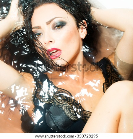 Closeup portrait of one sexual young sensory passionate attractive brunette woman with wet long curly hair and bright makeup lying in bath tab full of water taking shower in cloth, square picture - stock photo