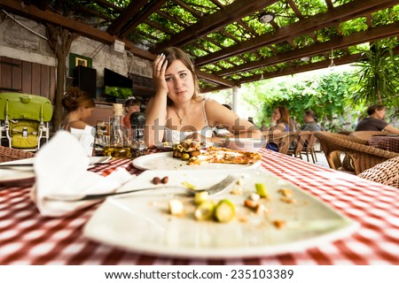 Closeup portrait of overeating woman looking at empty plates on table at restaurant - stock photo