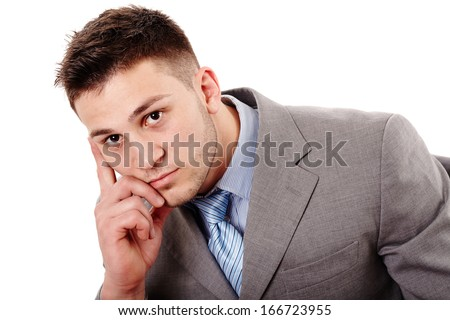 Closeup portrait of pensive businessman with hand on chin, isolated over white background