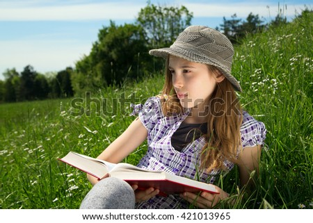 Closeup Portrait Of Pensive Young Girl With Book In Her Hands Sitting In The Grass On The Hillside And Thoughtfully Looking Sideways  - stock photo