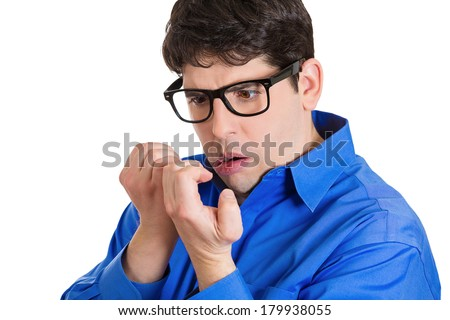 Closeup portrait of perfectionist man, obsessive compulsive, agitated funny young guy, anxiously staring at his fingernails, making sure they clean isolated on white background. Human face expressions - stock photo