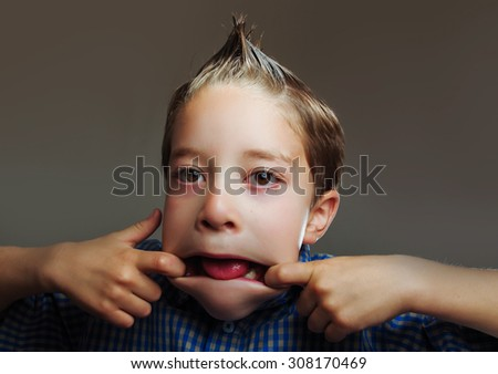 Closeup portrait of playful little boy making funny faces - stock photo