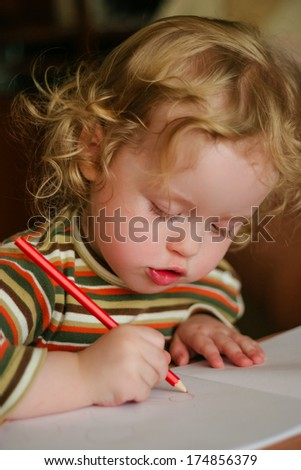 Closeup portrait of preschooler with strawberry blonde curly hairs who draws in the sketchbook by pencil and looks down - stock photo