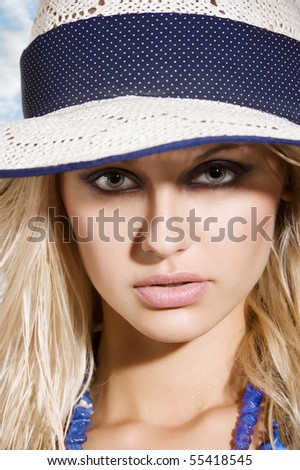 closeup portrait of pretty blond woman wearing a nice summer hat
