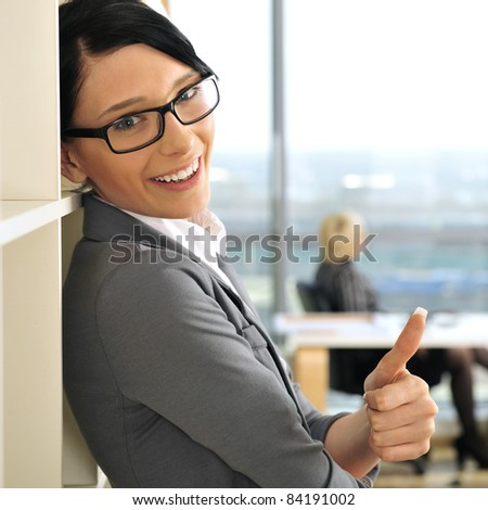 Closeup portrait of pretty cheerful business woman in an office environment - stock photo