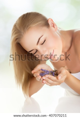 Closeup portrait of pretty girl enjoying gentle aroma of lavender flowers, closing eyes of pleasure, healthy lifestyle, body care, spending time in a spa salon - stock photo