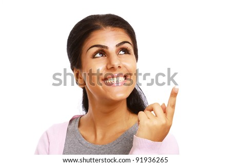 Closeup portrait of pretty happy young woman pointing at copyspace isolated on white background
